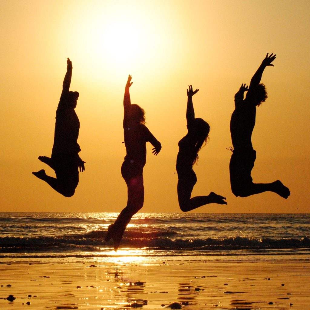 Sunset friends jumping in the air
