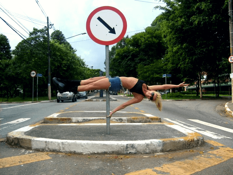Street pole dancing: a woman performs a #poledancing trick on a street sign in the middle of the road. #PoleFitness