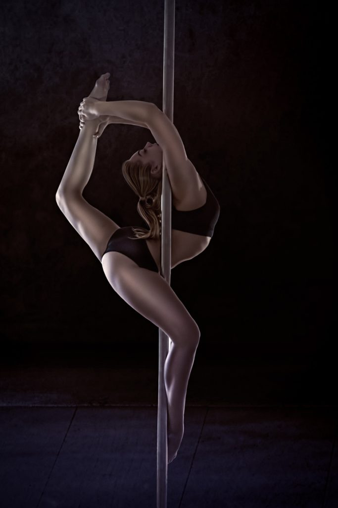 Pole dancer performing an eagle - a very advanced pole dancing trick