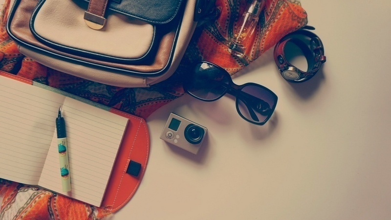 Stop wearing makeup to have more room in your bag. A ladies handbag with its contents: sunglasses, a camera, and a notebook