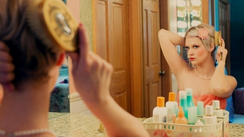 Stop wearing makeup: Get ready faster! Woman doing her hair in the mirror