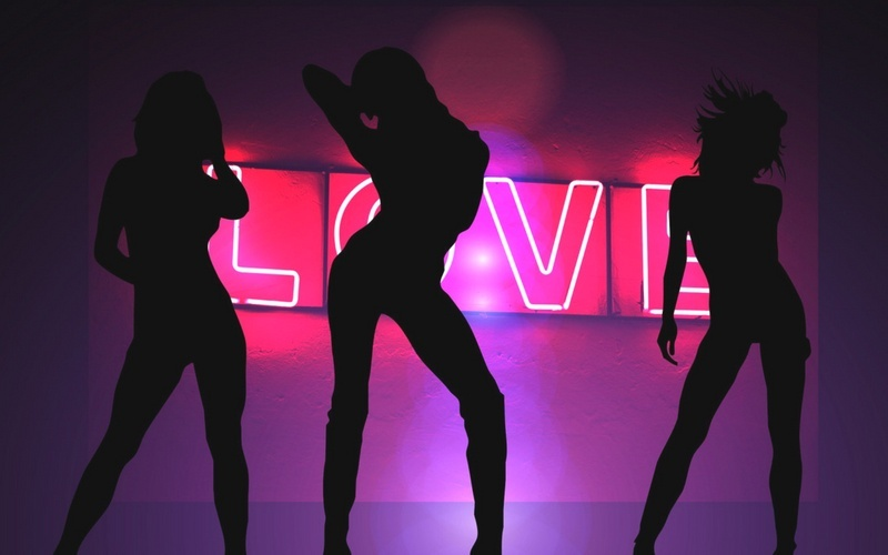 Silhouettes of Women Dancing in front of a glowing pink neon LOVE sign